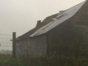 Barn roof torn off in the rain.