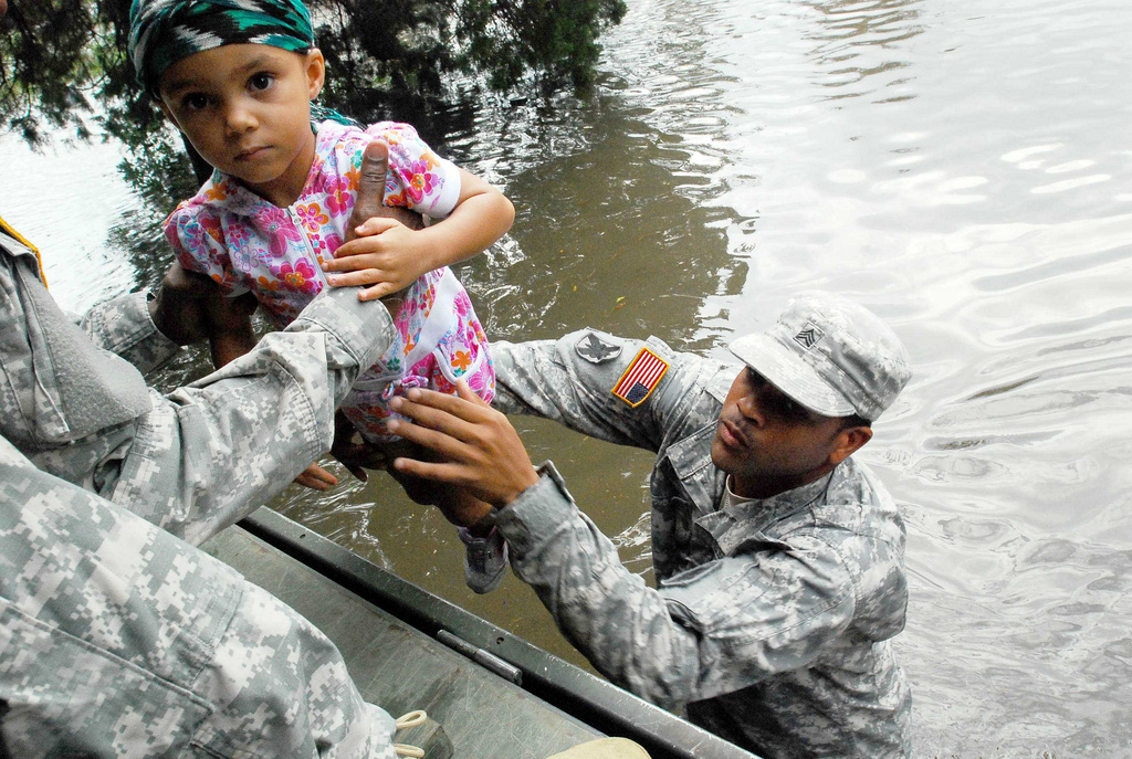 A soldier hands a child to another volunteer in a flood