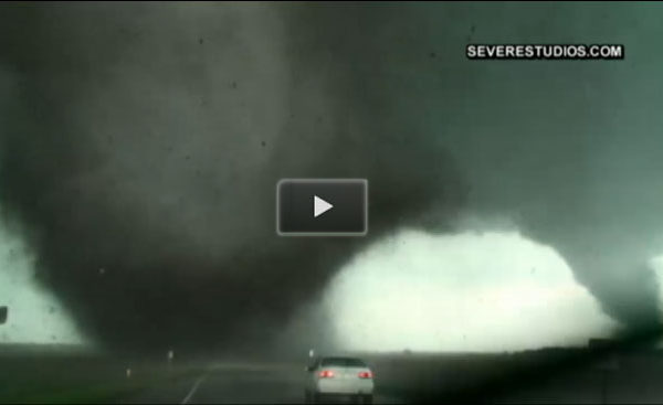 Midwest ravaged by destructive tornadoes, a car in the foreground, tornadoes in the back.